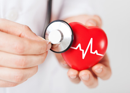 Photo pour healthcare and medicine concept - close up of male doctor hands holding red heart with ecg line and stethoscope - image libre de droit
