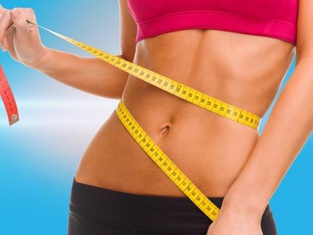 Foto de sport, fitness and diet concept - close up of trained belly with measuring tape - Imagen libre de derechos