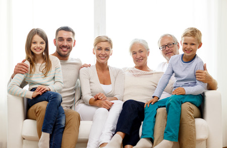Foto de family, happiness, generation and people concept - happy family sitting on couch at home - Imagen libre de derechos