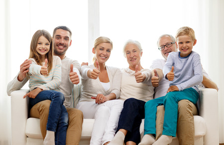 Photo pour family, happiness, generation and people concept - happy family sitting on couch and showing thumbs up gesture at home - image libre de droit