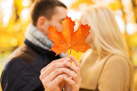 Photo pour love, relationship, family and people concept - close up of couple with maple leaf kissing in autumn park - image libre de droit