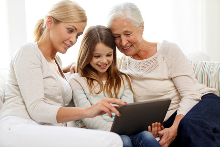 Foto de family, generation, technology and people concept - smiling mother, daughter and grandmother with tablet pc computer sitting on couch at home - Imagen libre de derechos