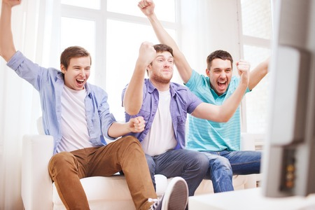 Foto de friendship, sports and entertainment concept - happy male friends supporting football team at home - Imagen libre de derechos