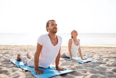 Foto de fitness, sport, friendship and lifestyle concept - couple making yoga exercises lying on mats outdoors - Imagen libre de derechos