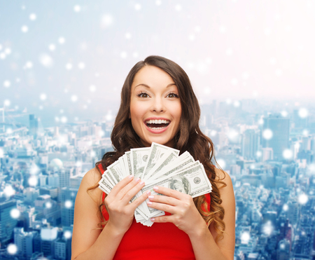 Foto de christmas, sale, banking, winning and holidays concept - smiling woman in red dress with us dollar money over snowy city background - Imagen libre de derechos