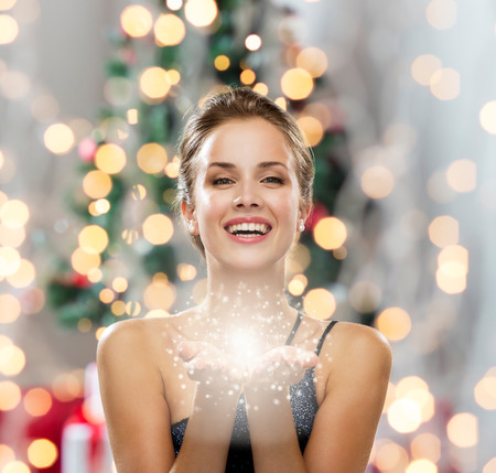 Photo pour people, holidays and magic concept - laughing woman in evening dress holding something over christmas tree and lights background - image libre de droit