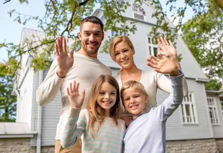 Foto de family, generation, home, gesture and people concept - happy family standing in front of house waving hands outdoors - Imagen libre de derechos