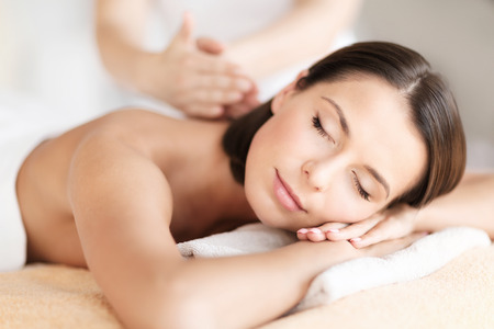 Photo pour health, beauty, resort and relaxation concept - beautiful woman with closed eyes in spa salon getting massage - image libre de droit