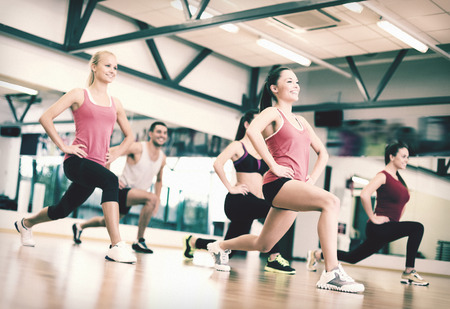 Foto de fitness, sport, training, gym and lifestyle concept - group of smiling people exercising in the gym - Imagen libre de derechos