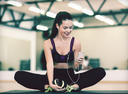 Photo for fitness, sport, training, gym, technology and lifestyle concept - smiling woman with smartphone - Royalty Free Image