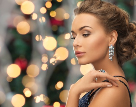 Photo pour people, holidays and glamour concept - beautiful woman in evening dress wearing ring and earrings over christmas lights background - image libre de droit