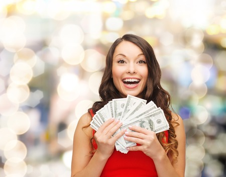 Foto de christmas, sale, banking, winning and holidays concept - smiling woman in red dress with us dollar money over lights background - Imagen libre de derechos