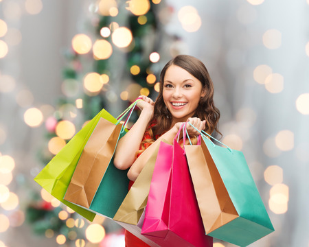 Photo pour sale, gifts, holidays and people concept - smiling woman with colorful shopping bags over living room and christmas tree background - image libre de droit