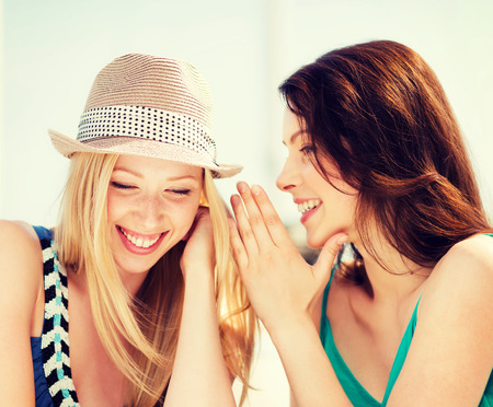 Photo for friendship, happiness and people concept - two smiling girls whispering gossip - Royalty Free Image