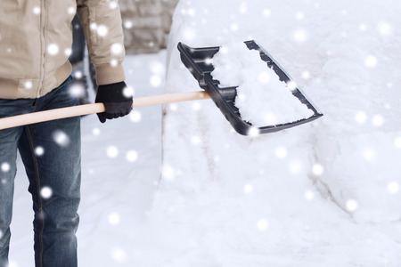 Foto de transportation, winter, people and vehicle concept - closeup of man digging snow with shovel near car - Imagen libre de derechos