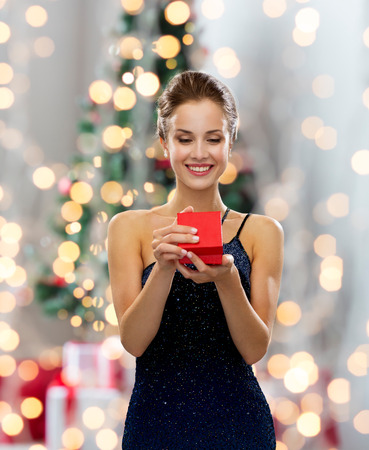 Photo pour smiling woman in dress holding red gift box over christmas tree lights background - image libre de droit
