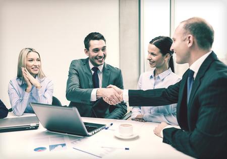Photo pour  two smiling businessman shaking hands in office - image libre de droit