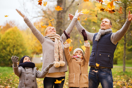Foto de family, childhood, season and people concept - happy family playing with autumn leaves in park - Imagen libre de derechos