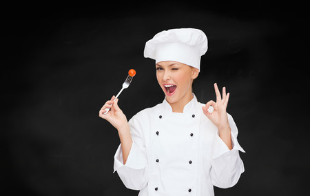 Foto per cooking and food concept - smiling female chef, cook or baker with fork and tomato showing ok sign - Immagine Royalty Free