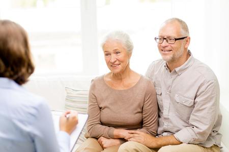 Foto de family, relations, age and people concept - happy senior couple and psychologist or social worker at home - Imagen libre de derechos