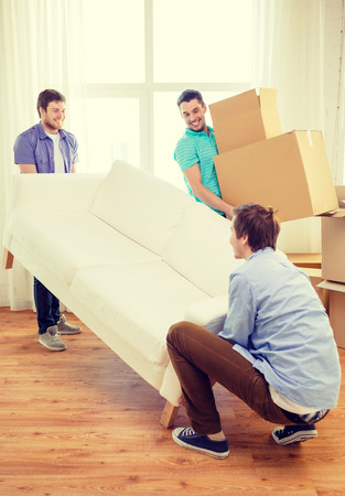 Photo for moving, real estate and friendship concept - smiling male friends with sofa and boxes at new home - Royalty Free Image