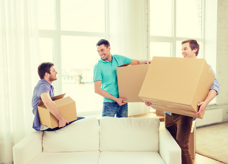 Photo for moving, real estate and friendship concept - smiling male friends carrying boxes at new place - Royalty Free Image