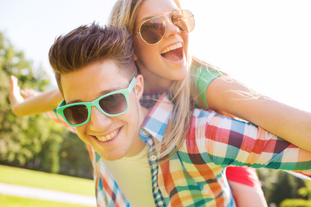 Foto de holidays, vacation, love and friendship concept - smiling teen couple in sunglasses having fun in summer park - Imagen libre de derechos