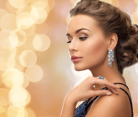 Foto de people, holidays and glamour concept - beautiful woman in evening dress wearing ring and earrings over beige lights background - Imagen libre de derechos