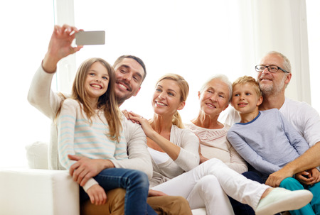 Foto de family, happiness, generation and people concept - happy family sitting on couch and making selfie with smartphone at home - Imagen libre de derechos