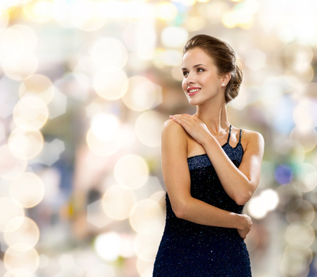 Photo pour people, holidays and glamour concept - smiling woman in evening dress over lights background - image libre de droit