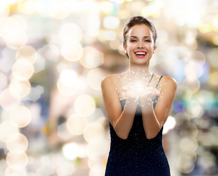 Photo for holidays and people concept - laughing woman in evening dress holding something over lights background - Royalty Free Image