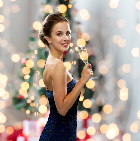 Foto de party, drinks, holidays, people and celebration concept - smiling woman in evening dress with glass of sparkling wine over christmas tree lights background - Imagen libre de derechos
