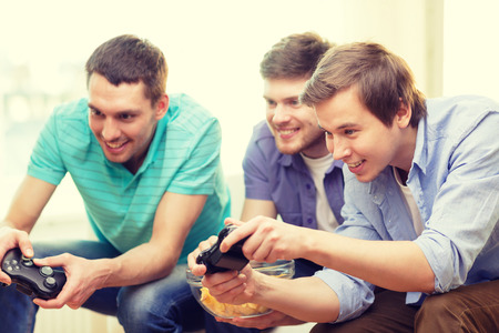 Photo pour friendship, technology, games and home concept - smiling male friends playing video games at home - image libre de droit