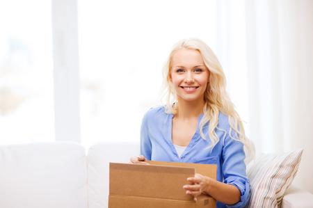 Foto de transportation, post and people concept - smiling young woman opening cardboard box at home - Imagen libre de derechos