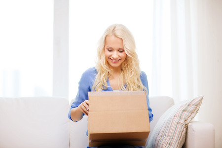 Foto de transportation, post and people concept - smiling young woman opening cardboard box at home - Imagen libre de derechos