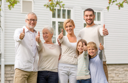 Foto de family, happiness, generation, home and people concept - happy family standing in front of house outdoors - Imagen libre de derechos