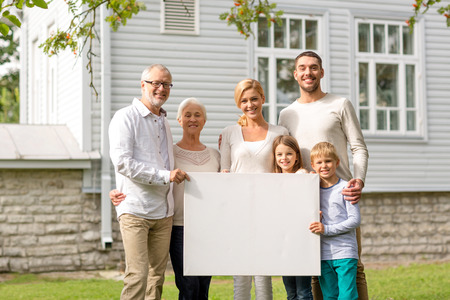 Foto de family, happiness, generation, home and people concept - happy family standing in front of house with white blank board outdoors - Imagen libre de derechos