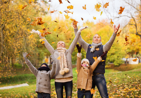 Photo for family, childhood, season and people concept - happy family playing with autumn leaves in park - Royalty Free Image
