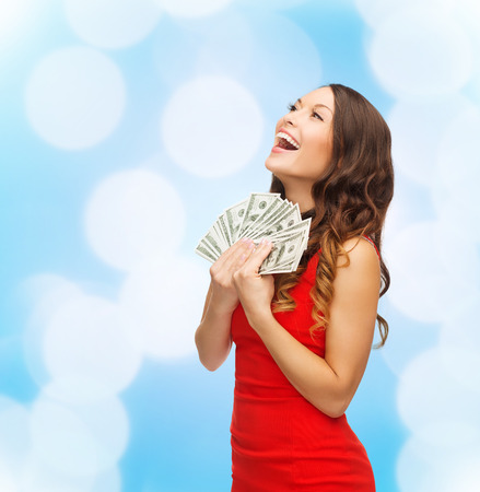 Foto de christmas, holidays, sale, banking and people concept - smiling woman in red dress with us dollar money over blue lights - Imagen libre de derechos