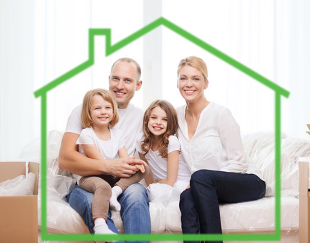 Photo for family, children, accommodation and home concept - smiling parents and two little girls at home behind green house symbol - Royalty Free Image