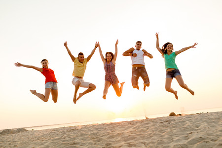 Foto de friendship, summer vacation, holidays, party and people concept - group of smiling friends dancing and jumping on beach - Imagen libre de derechos