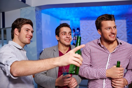 Photo for nightlife, party, friendship, leisure and people concept - group of smiling male friends with beer bottles drinking in nightclub - Royalty Free Image