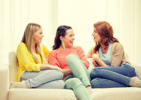 Photo for friendship and happiness concept - three girlfriends having a talk at home - Royalty Free Image