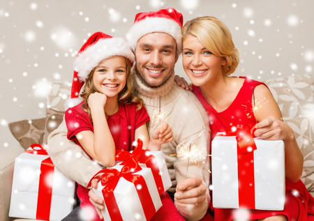Photo pour christmas, holidays, happiness and people concept - smiling family in santa helper hats with many gift boxes and sparklers at home - image libre de droit
