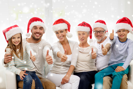 Foto de family, happiness, generation, holidays and people concept - happy family in santa helper hats sitting on couch and showing thumbs up gesture at home - Imagen libre de derechos