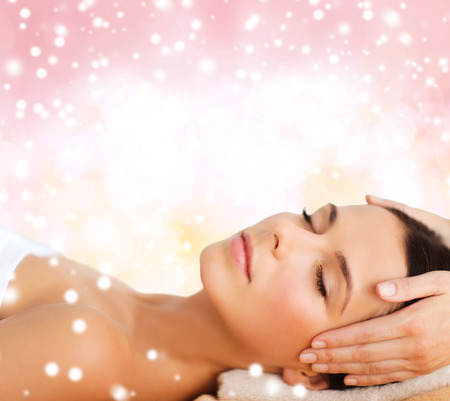 Photo pour beauty, health, holidays, people and spa concept - beautiful woman in spa salon getting face or head massage over pink background - image libre de droit