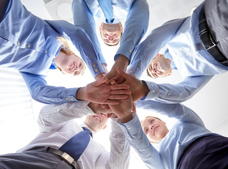 Photo for business, people and teamwork concept - smiling group of businesspeople standing in circle and putting hands on top of each other - Royalty Free Image