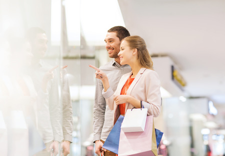 Foto de sale, consumerism and people concept - happy young couple with shopping bags pointing finger to shop window in mall - Imagen libre de derechos