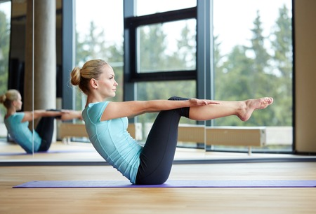 Photo for fitness, sport, training and people concept - smiling woman doing abdominal exercises on mat in gym - Royalty Free Image