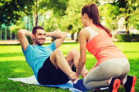 Photo pour fitness, sport, training, teamwork and lifestyle concept - smiling man with personal trainer doing exercises on mat outdoors - image libre de droit